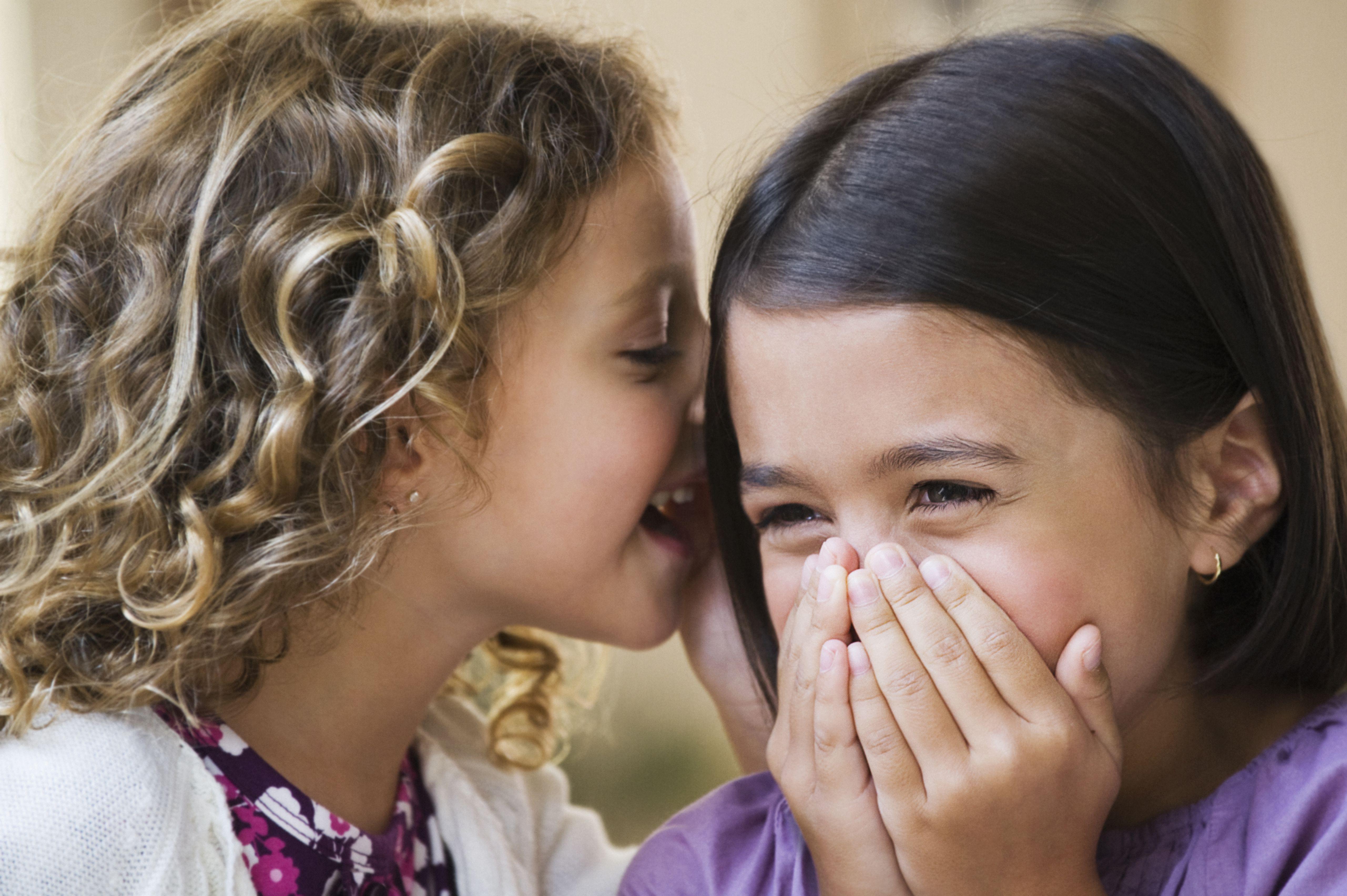 Two kids telling secrets