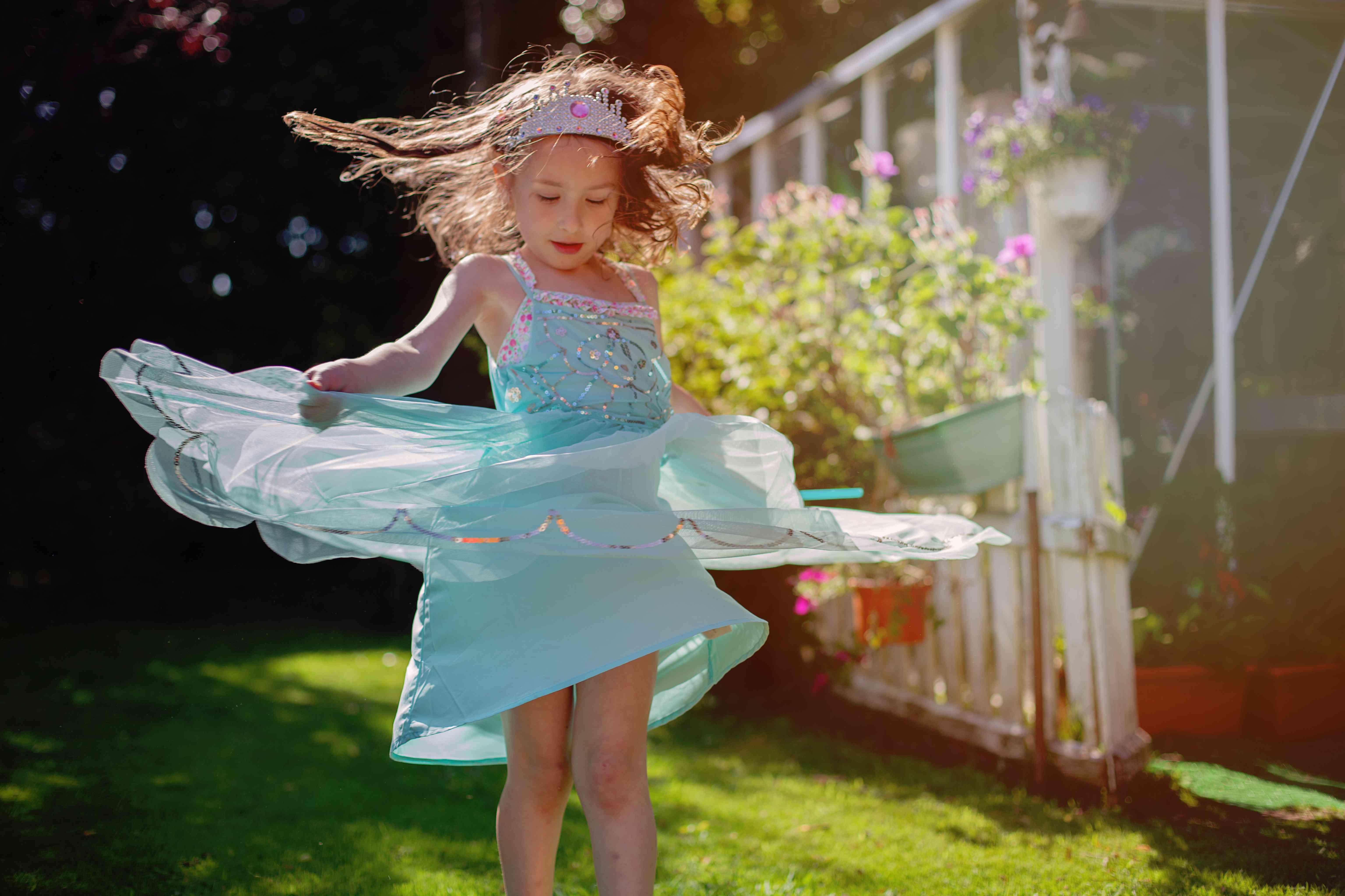 girl ( 5) dancing in field in princess dress