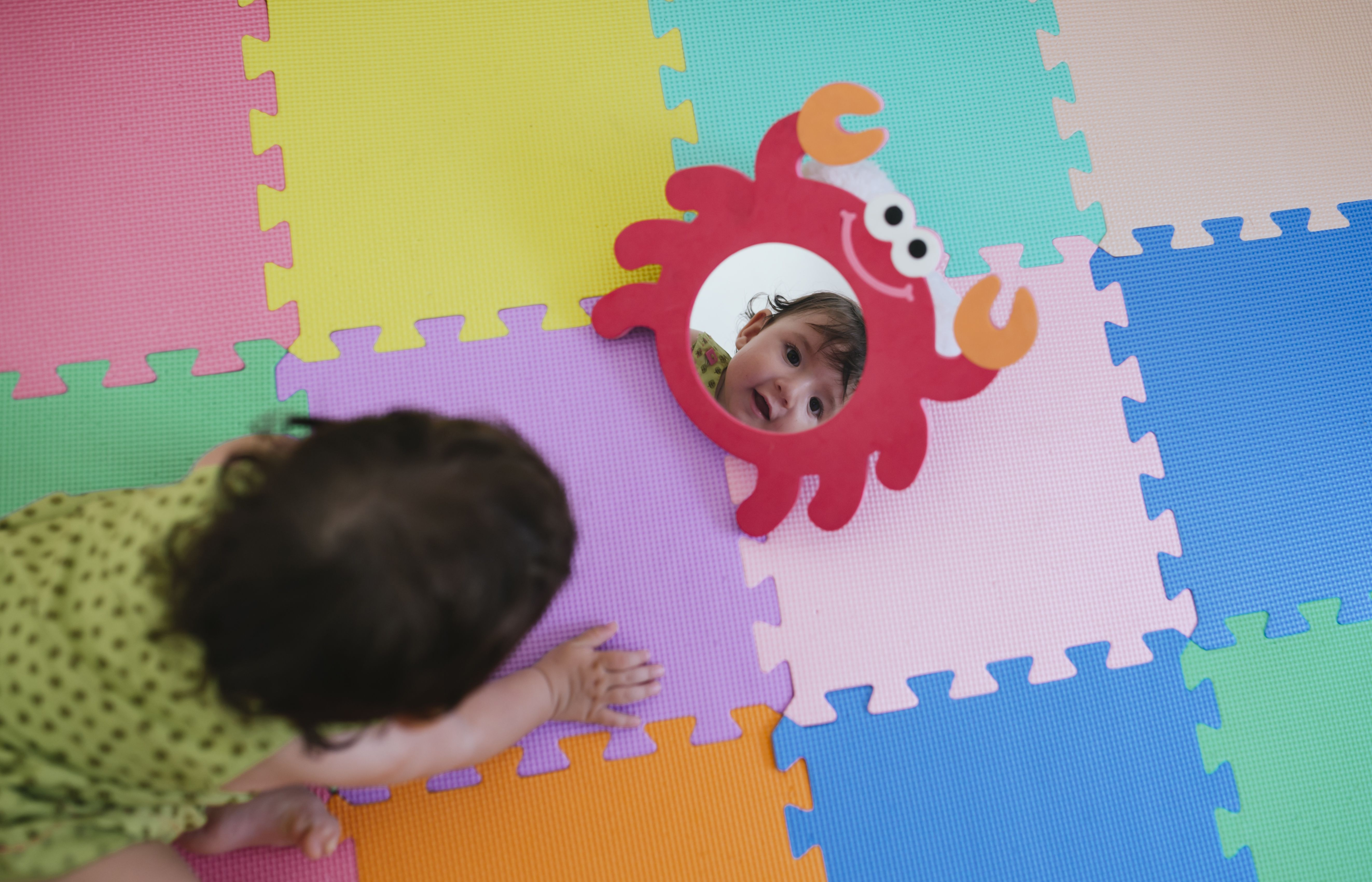 Cute baby girl looking at herself in a toy mirror on a colorful puzzle floor mat