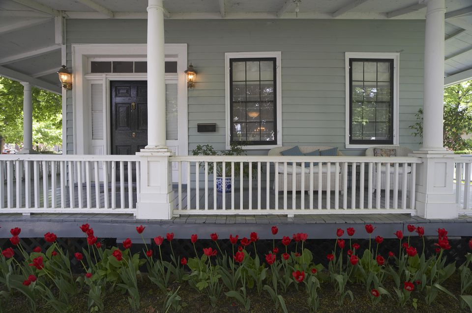 Dark-colored window sashes and door, white window and door trim, white porch railing and columns and porch ceiling, green exterior siding, all behind a bed or red roses