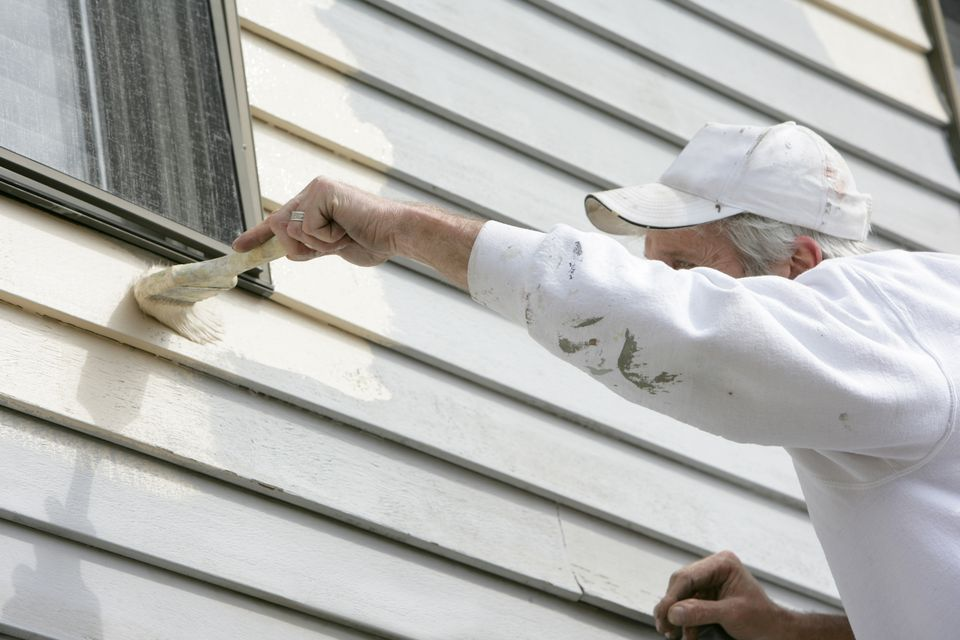 A house painter works around the window trim