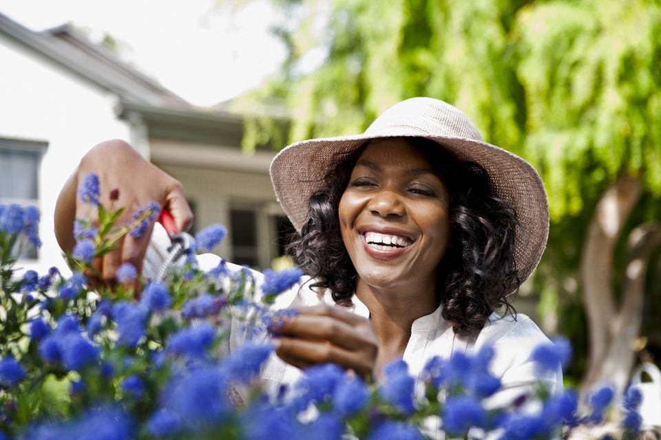 Smiling woman pruning flowers in garden