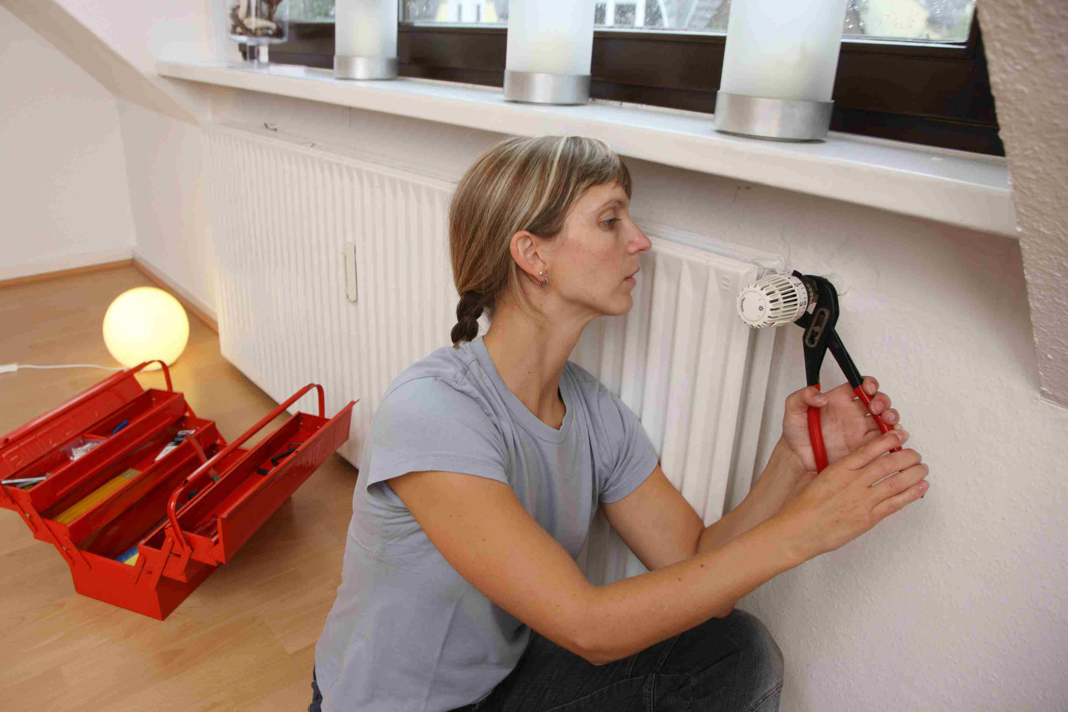 Woman using a wrench to tighten a thermostatic radiator valve.