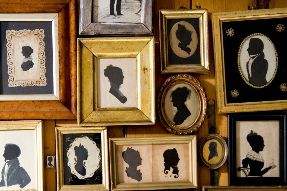 Collection of vintage silhouettes hanging on the wall.