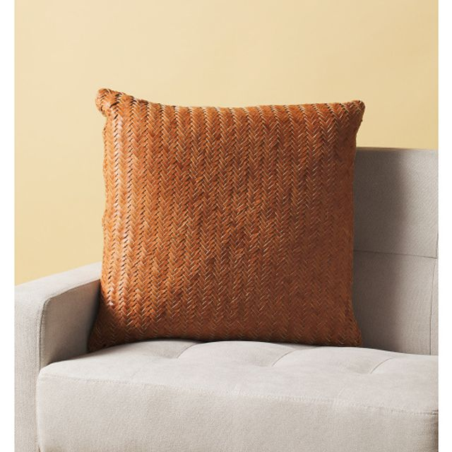 A woven leather throw pillow on a couch