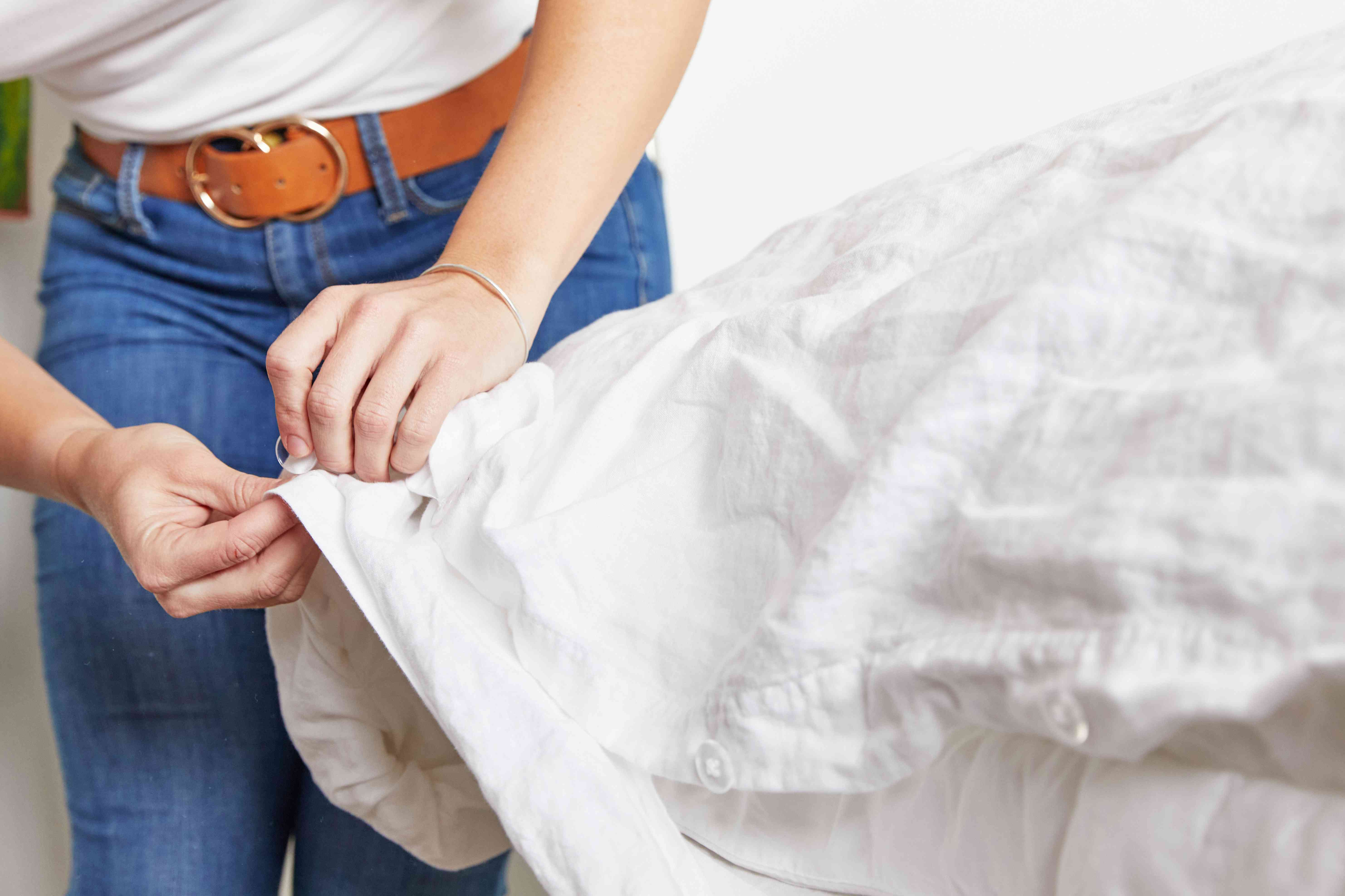 woman buttoning up a duvet cover