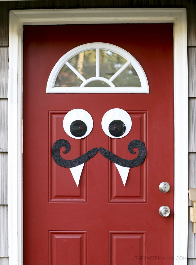 A red door decorated with a face