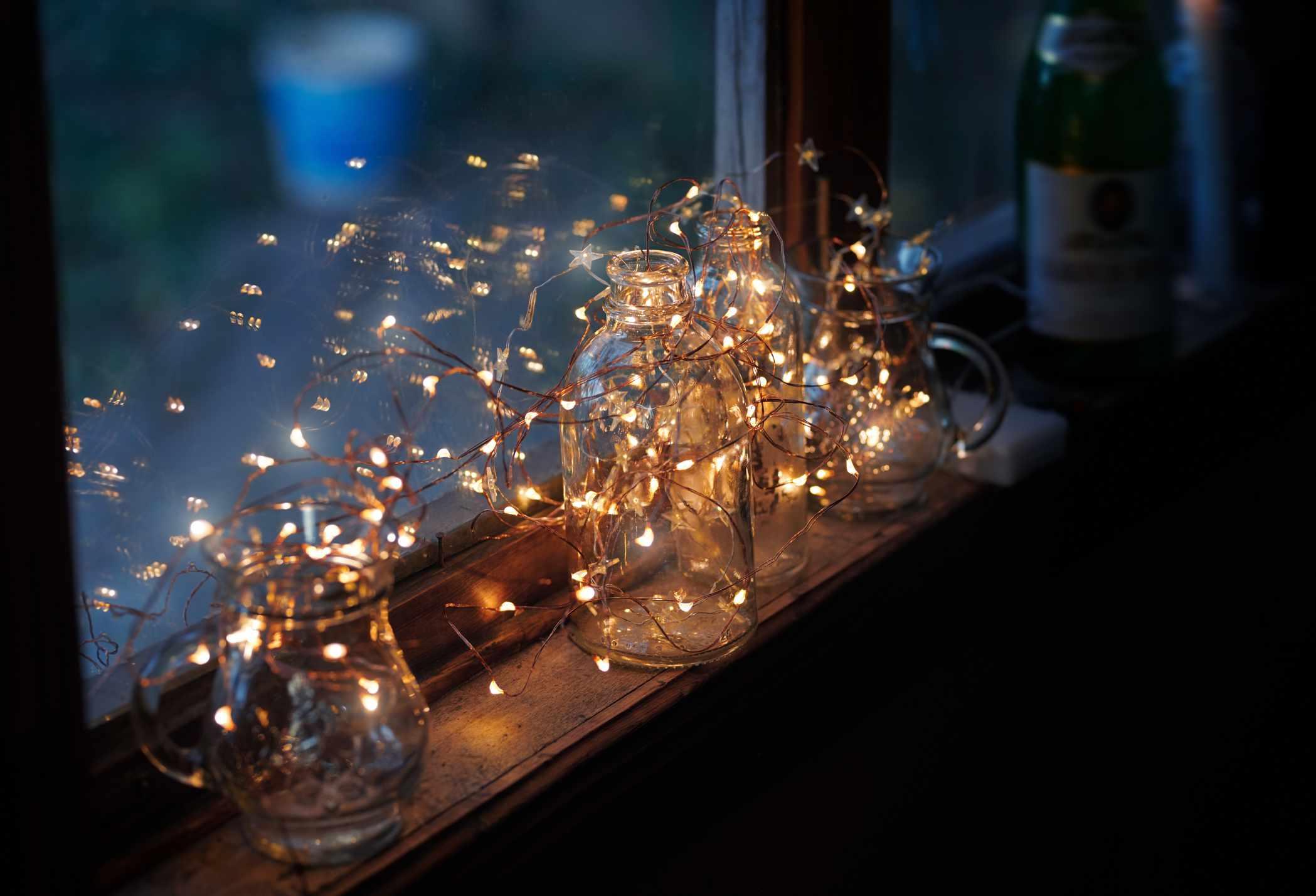 alféizar de la ventana decorado con cristalería y luces navideñas