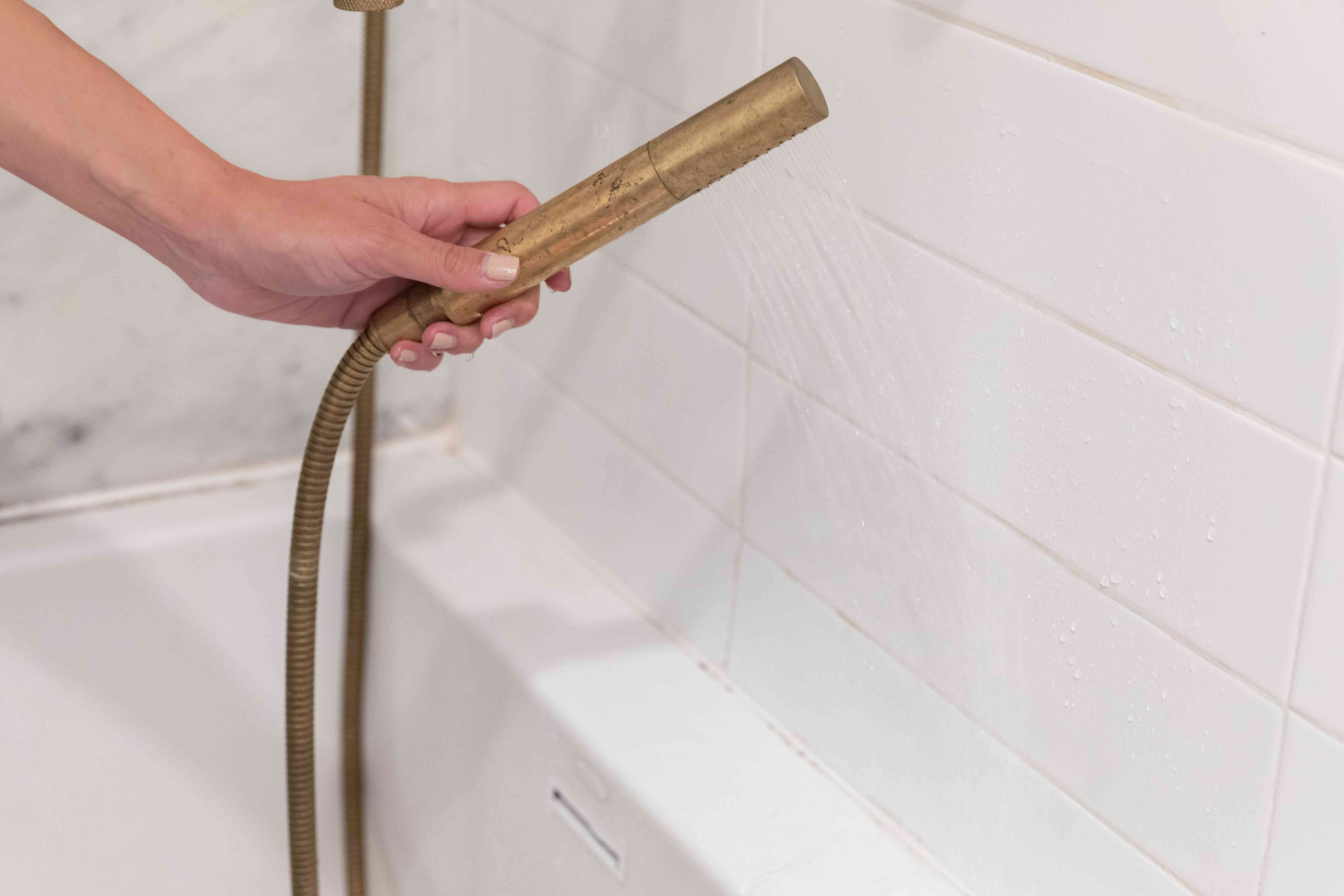 White bathroom wall being rinsed with brass shower hose after scrubbing pink mold