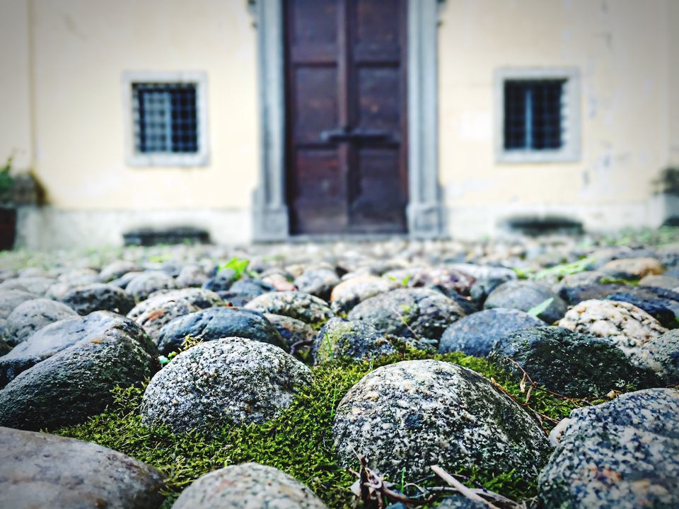Close-Up Of Stones On Field Against House