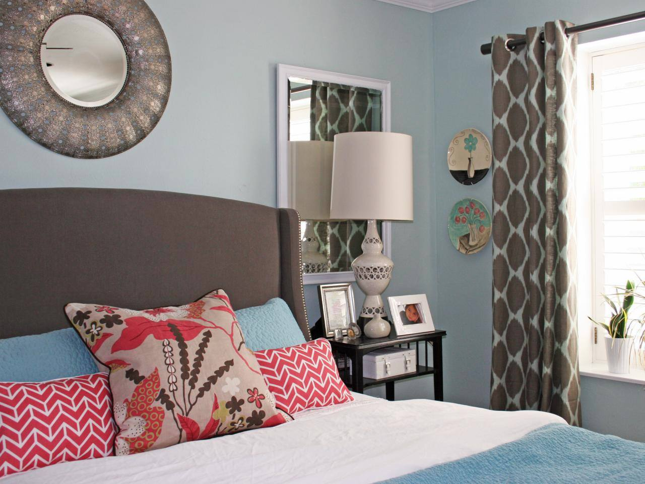 Habitación azul claro, cortinas marrones y almohadas rojas .