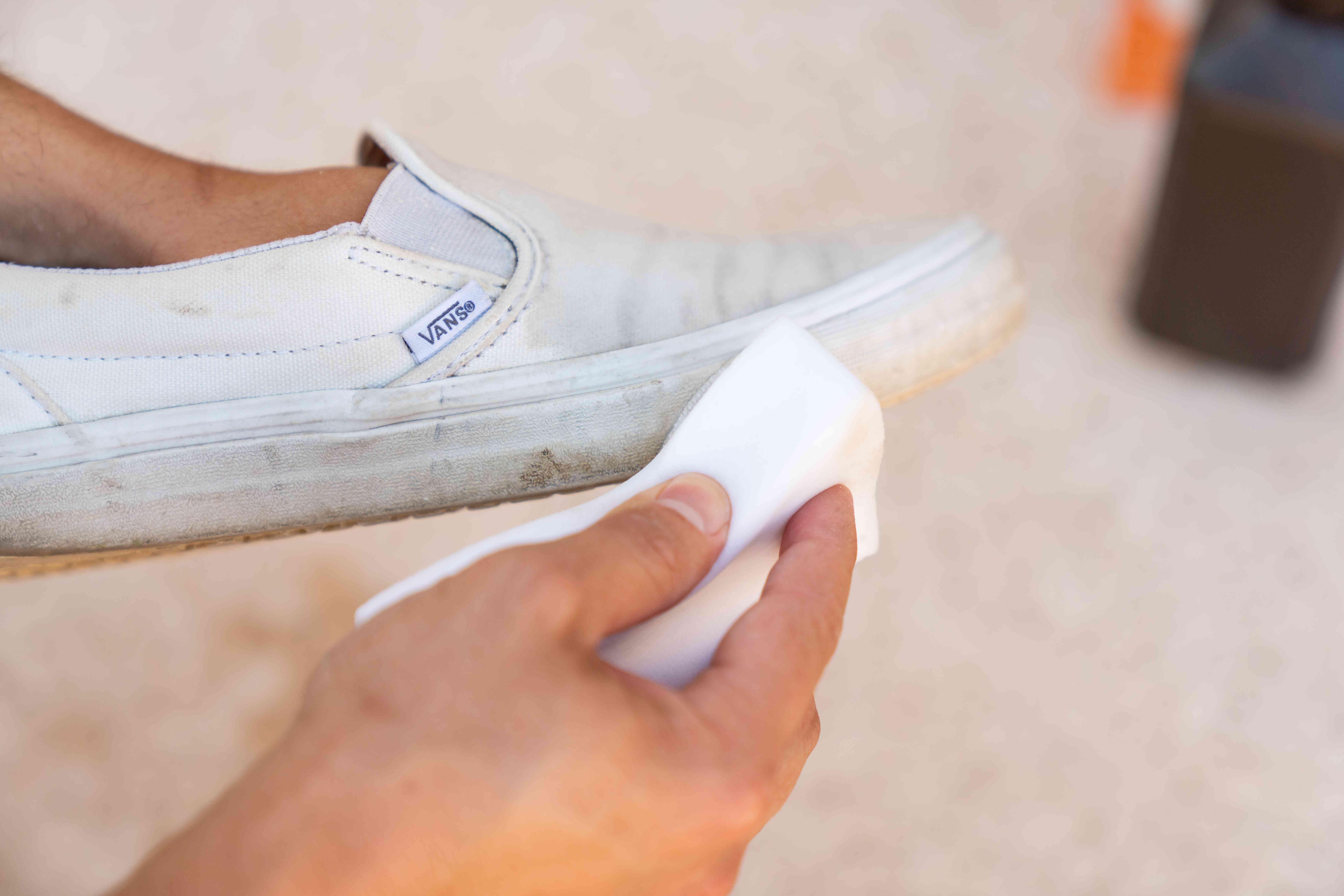 Dirty white van's rubber soles scrubbed by melamine sponge