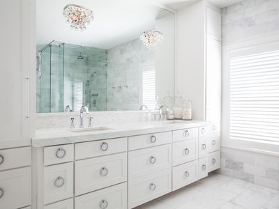 two crystal chandeliers in traditional marble bathroom