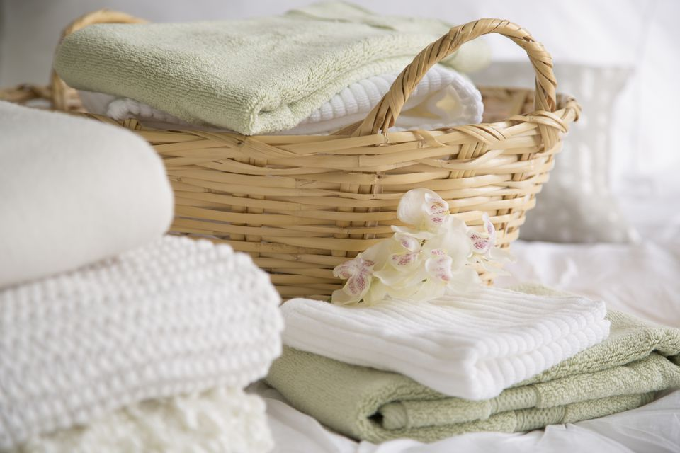 Folded towels and bedding in wicker basket.