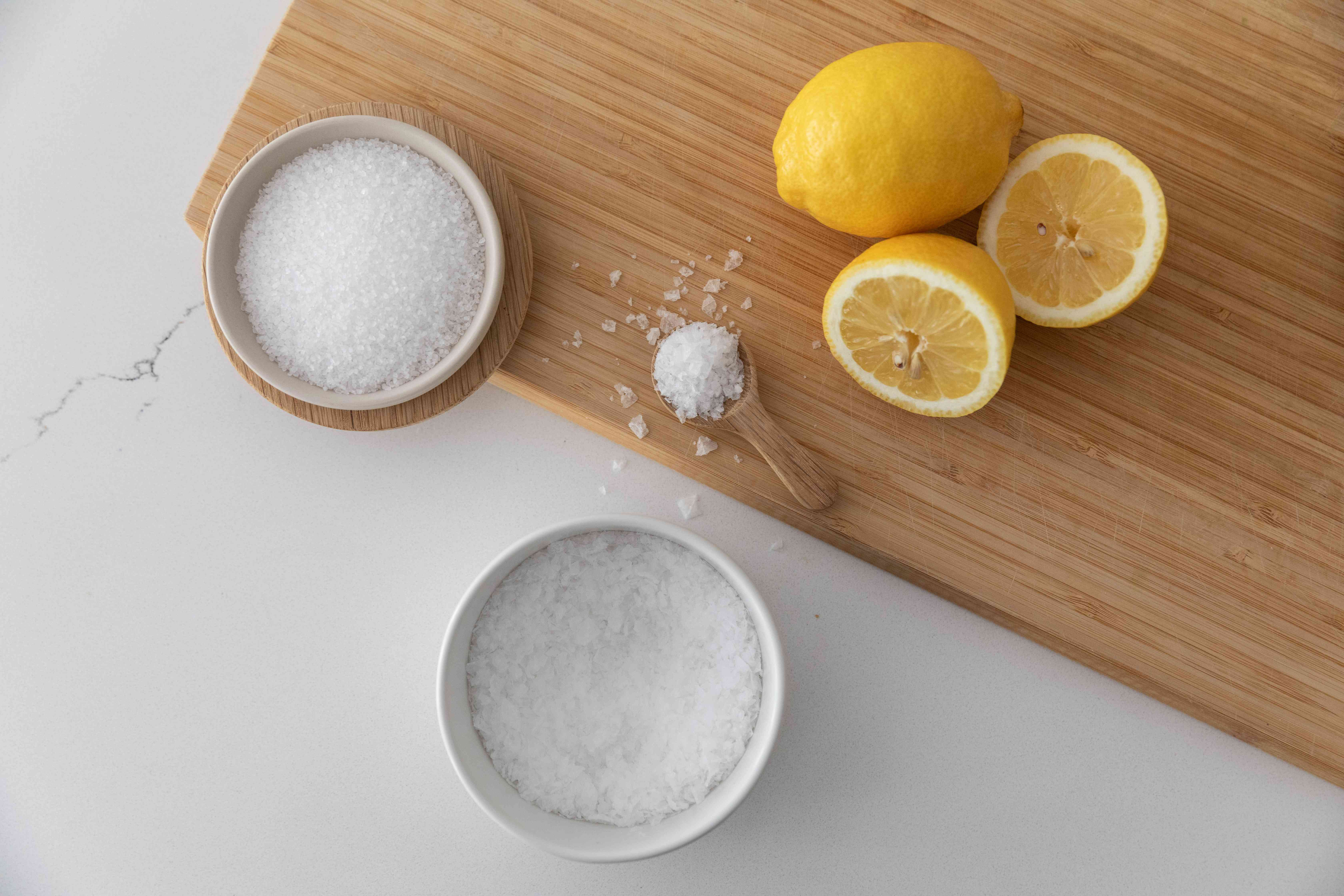 Cutting board with cut lemons and bowls of salt with spoon full of salt