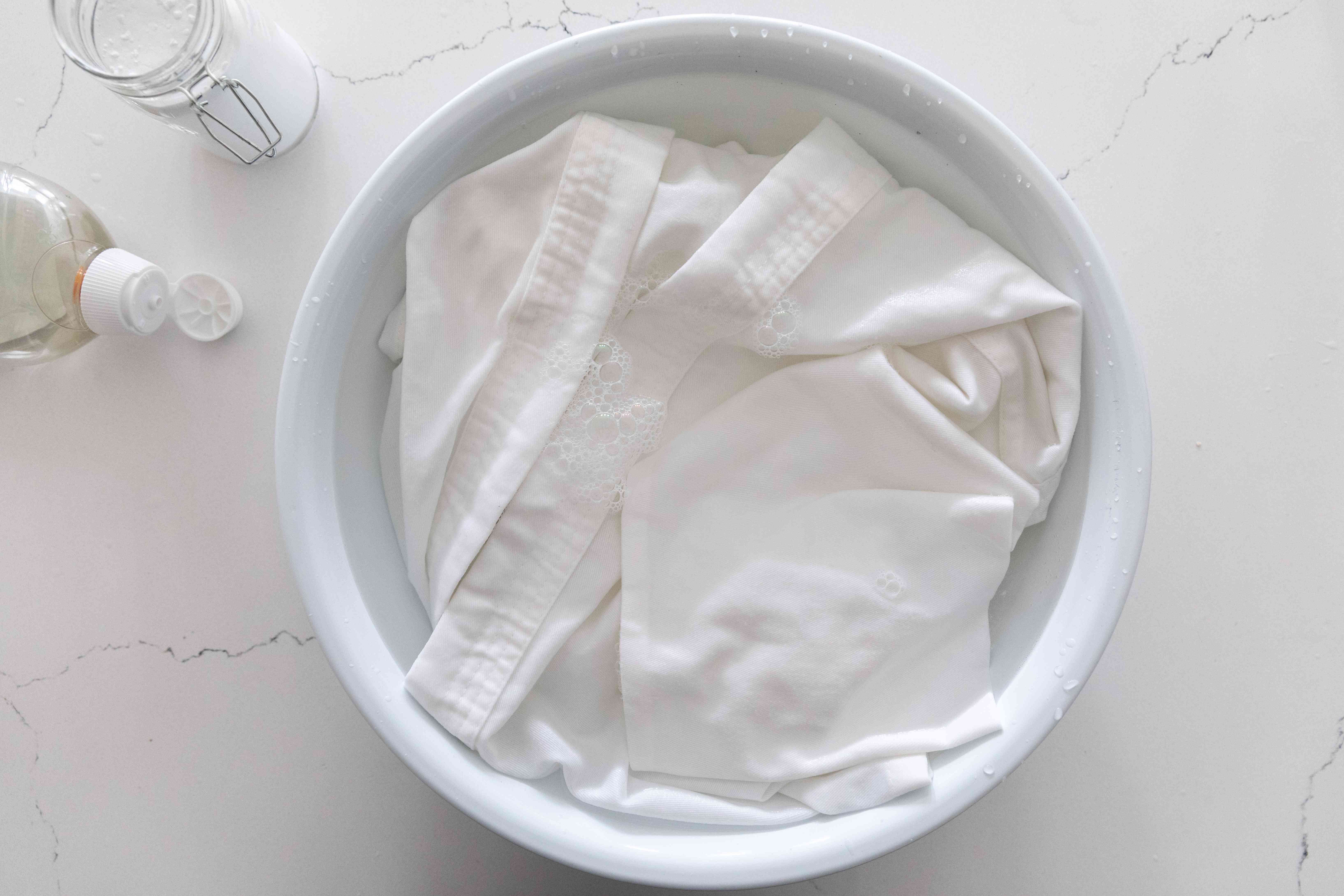 Karate uniforms soaked in large white bowl with heavy-duty laundry detergent and baking soda