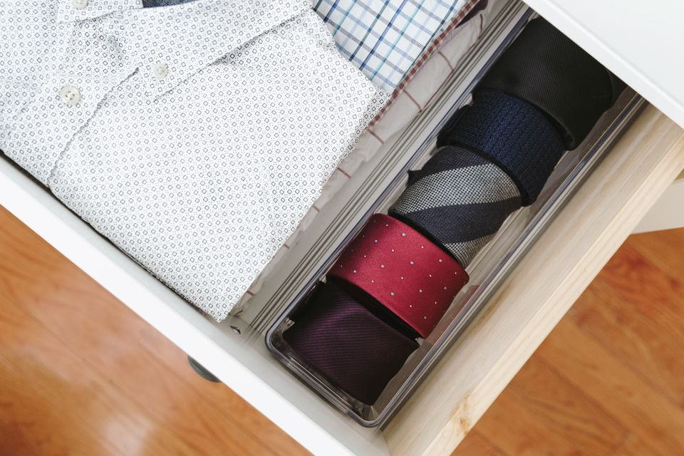 ties rolled up and stored in a plastic bin