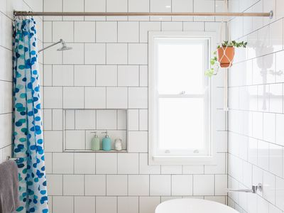 Small bathroom with white tile walls and blue shower curtain.
