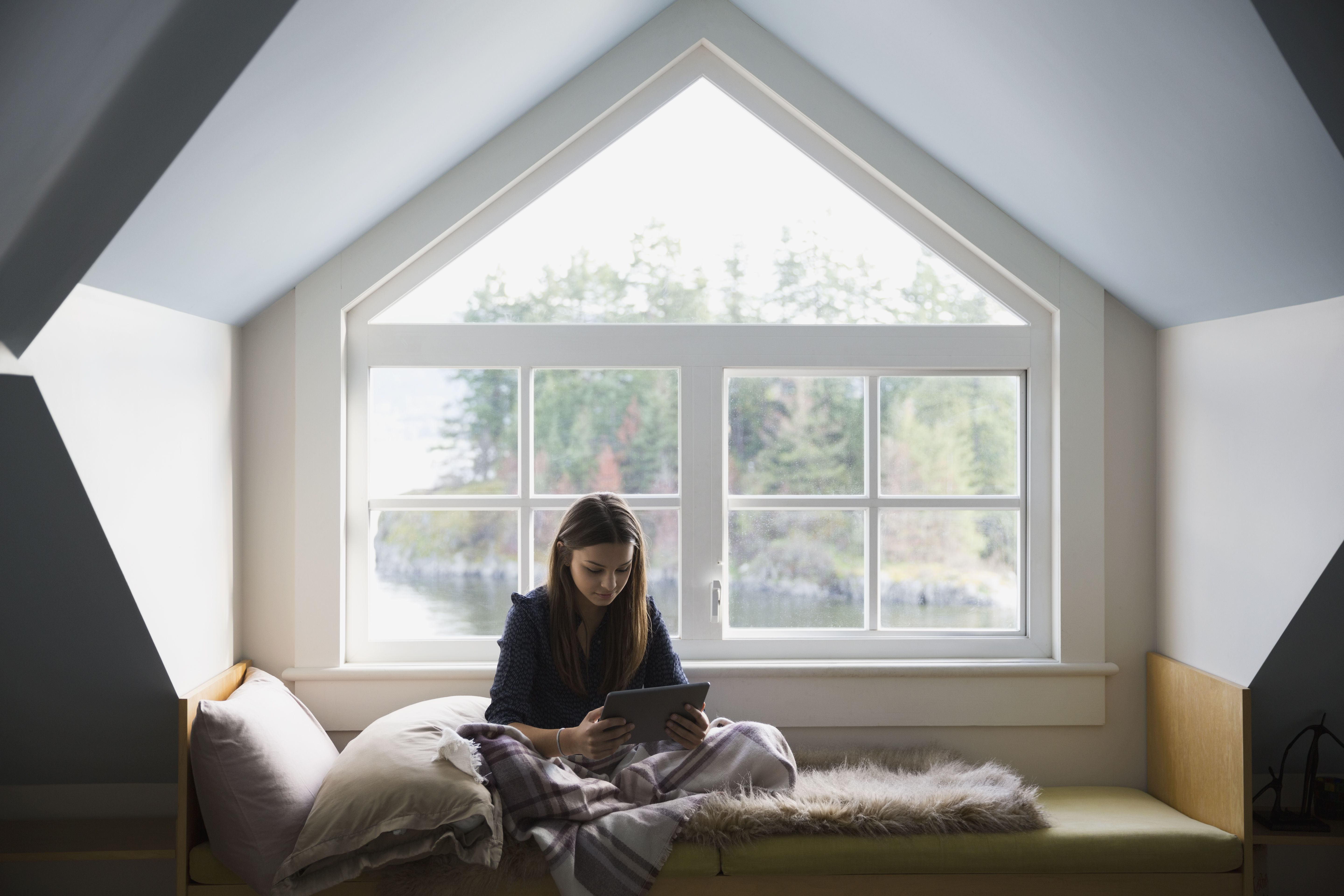 Teenage girl with digital tablet in dormer alcove window seat