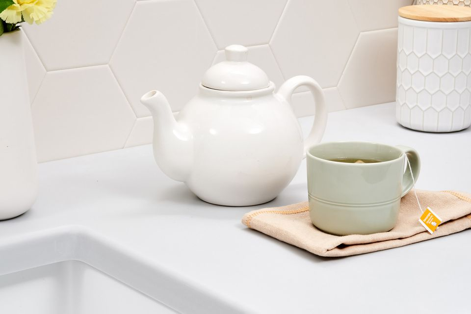 teapot and cup of tea with herbs in the kitchen