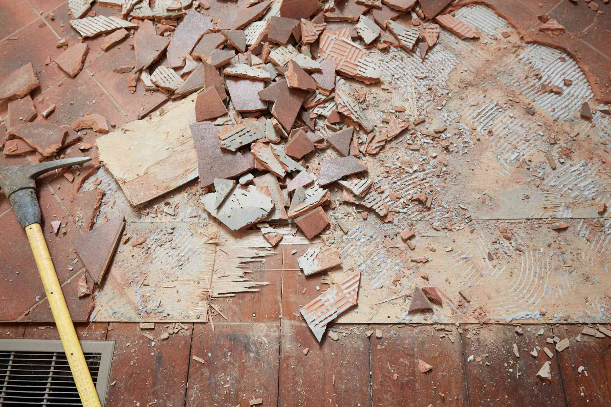 Floor edge with brown ceramic tile broken into smaller pieces with masonry chisel