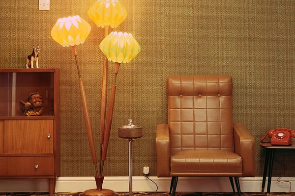 1960s style lounge with leather couch, lamp, and red telephone on an end table.