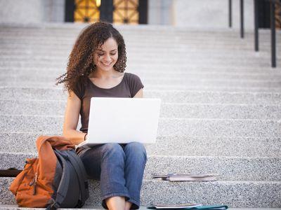 Caucasian college student using laptop outdoors