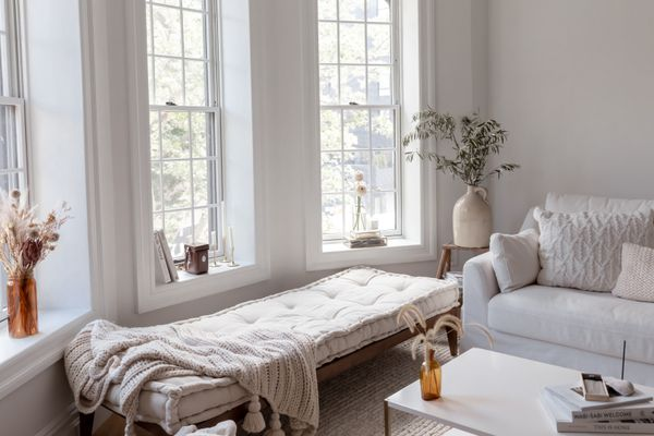 Wabi-sabi home with neutral living room colors and furniture near tall windows