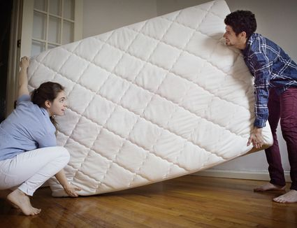 Couple carrying mattress in room