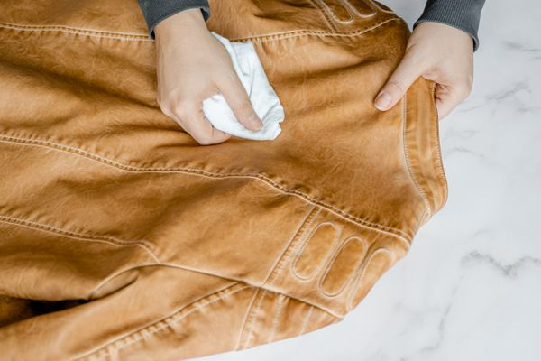 Leather jacket being cleaned with white cloth in hand