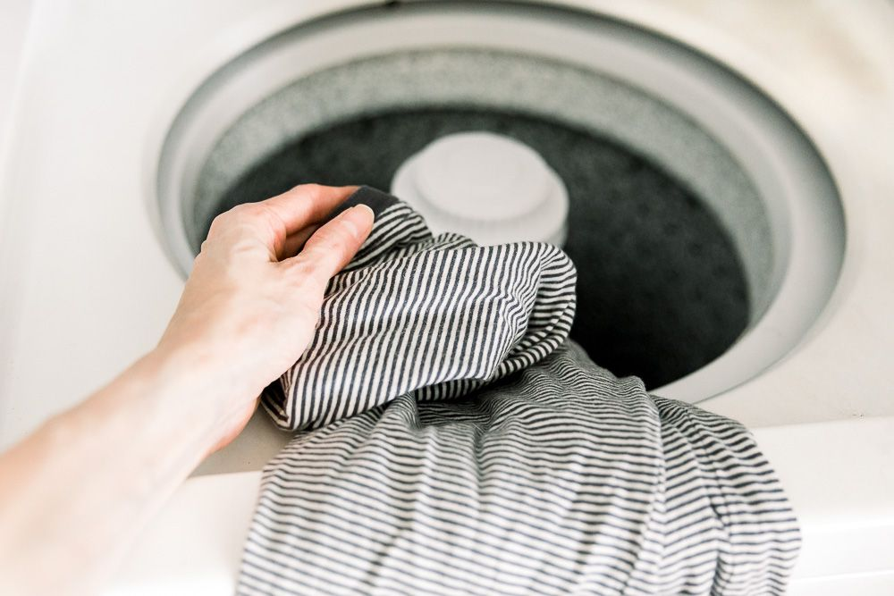 person loading a garment into the washer