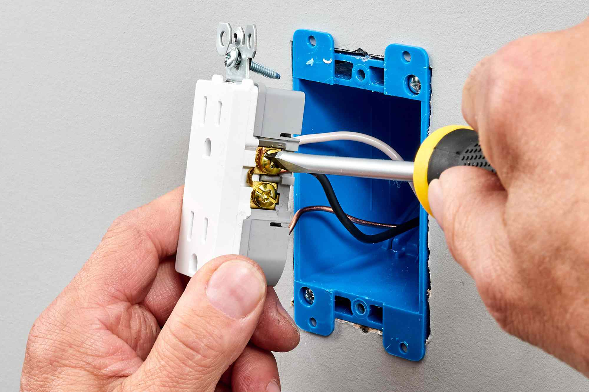 New outlet receptacle attached to wires and securing screw terminals with screw driver