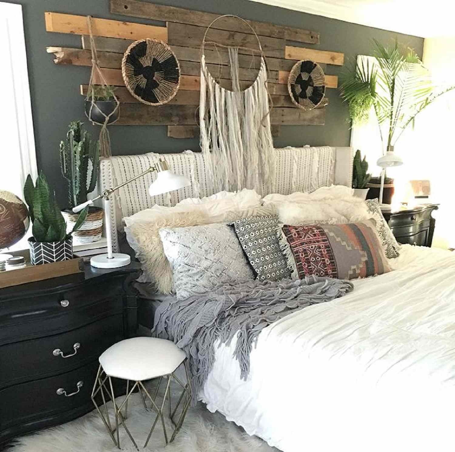 Eclectic neutral bedroom with bed, pillows, and wooden headboard.