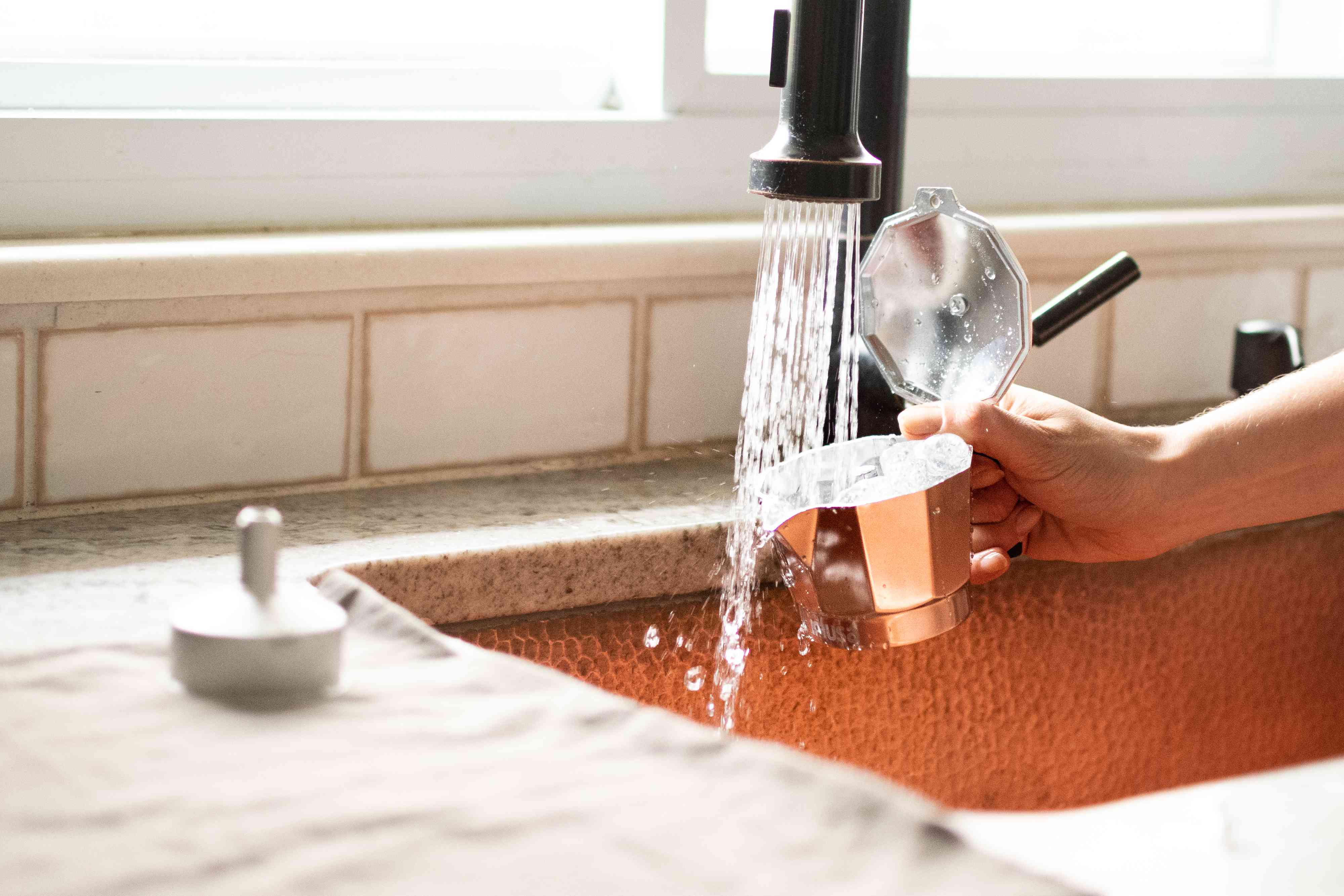 Moka pot compartments rinsed under running faucet with hot water