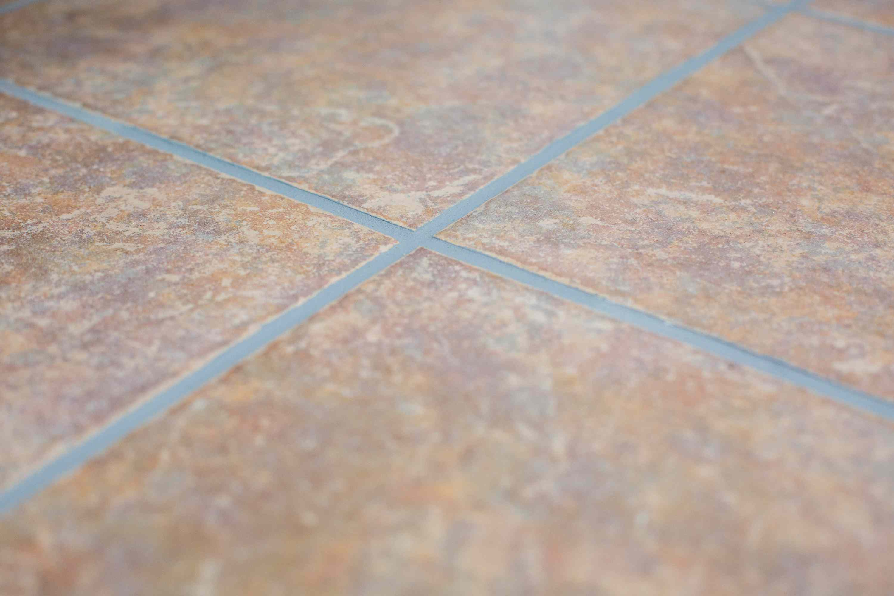 Newly applied grout colorant on brown tile air drying closeup