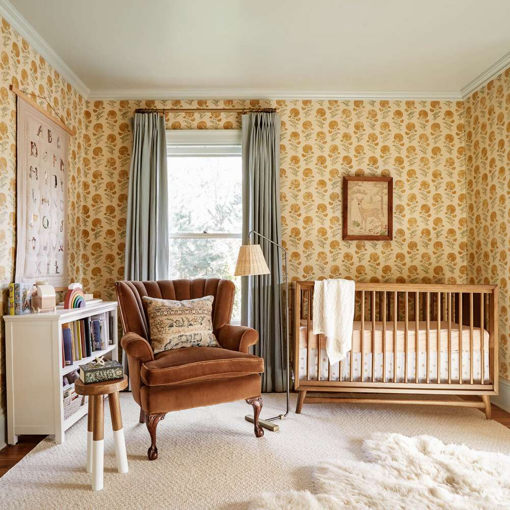 nursery with yellow floral wallpaper, cushion chair, white fluffy rug on the floor