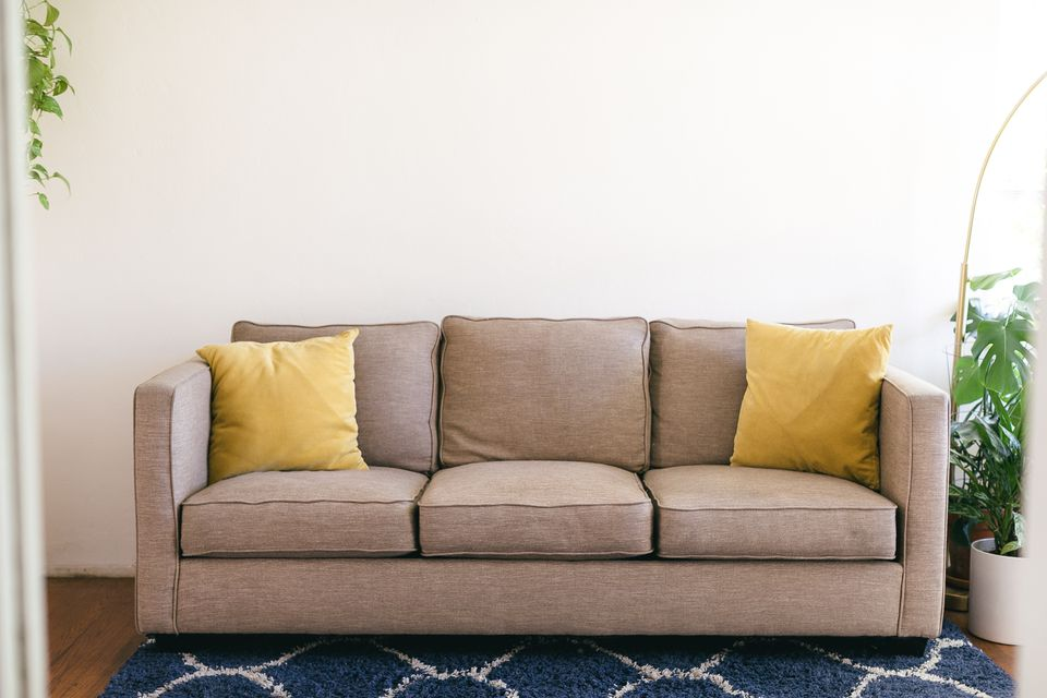 Tan couch with yellow cushions next to houseplants and blue rug