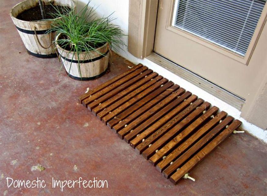 A wooden mat on a front porch