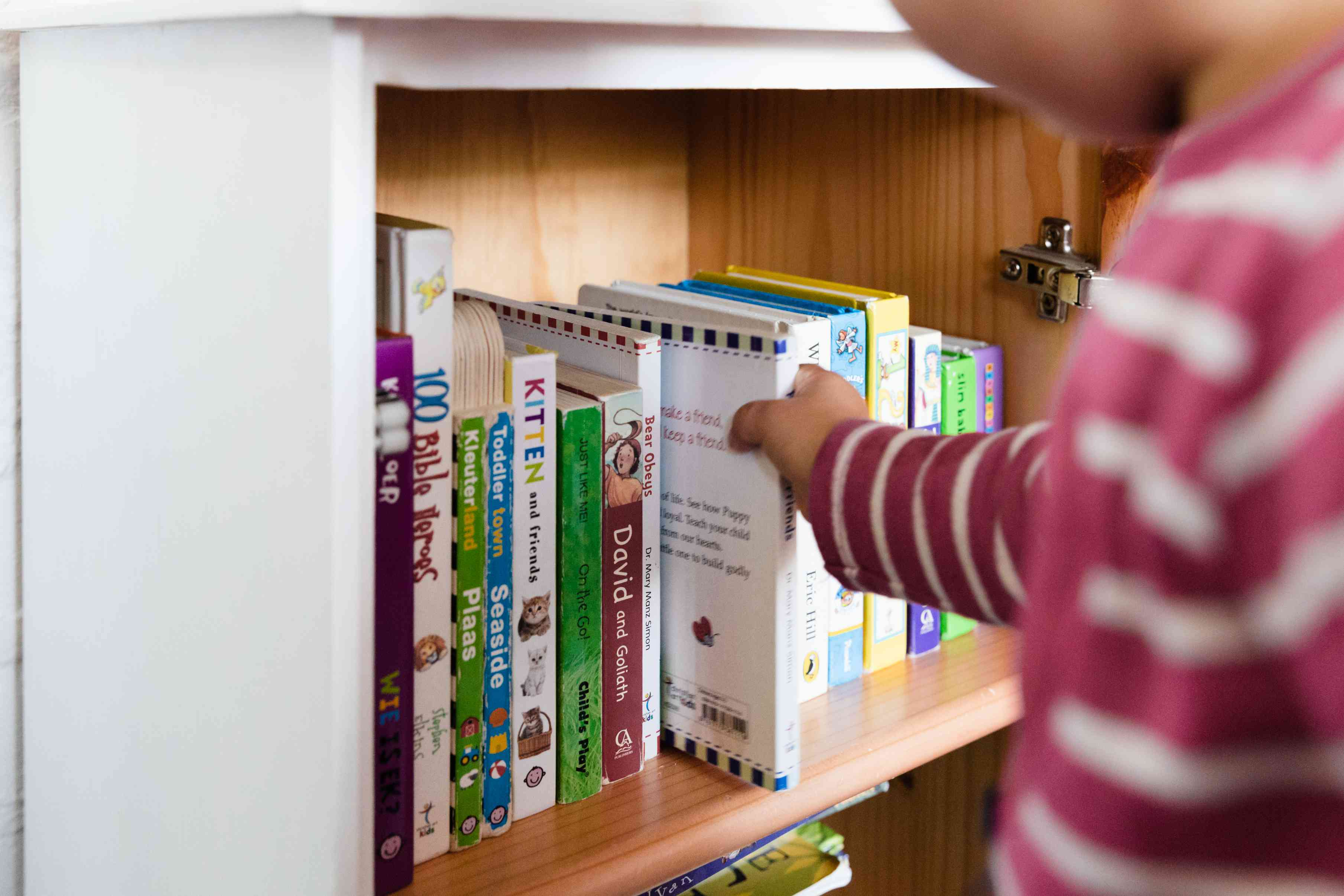 child putting away books