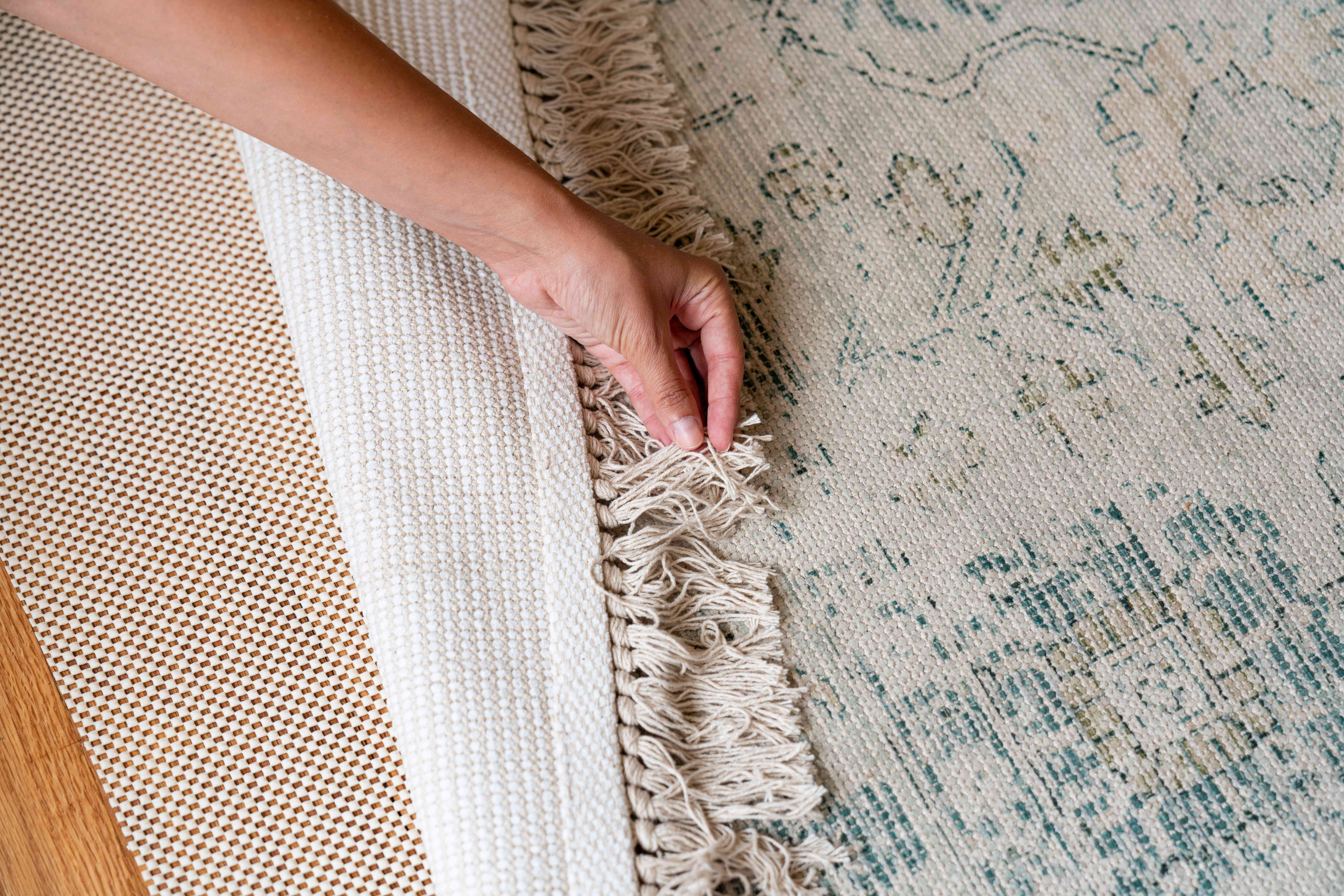 Tan and blue hand-knotted rug flipped over to show hand-made pattern