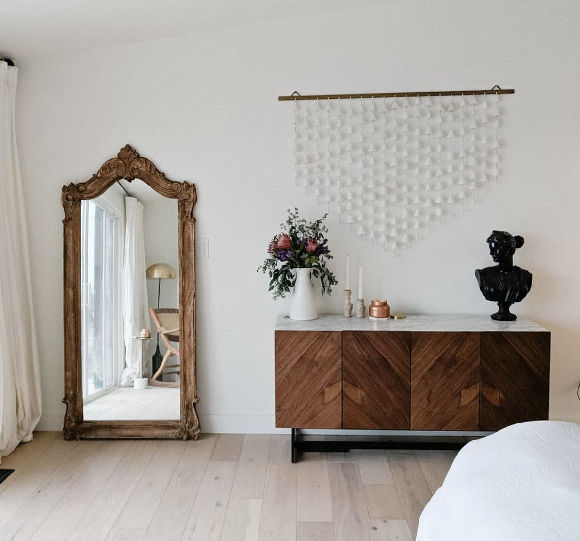 minimalist bedroom with rustic wooden mirror propped in corner