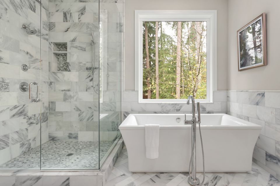 Master bathroom interior in luxury home with large shower with elegant tile and soaking bathtub. Includes large window with view of trees.