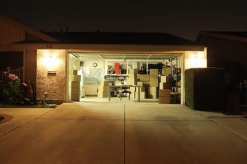 Illuminated garage with open door and lots of boxes.