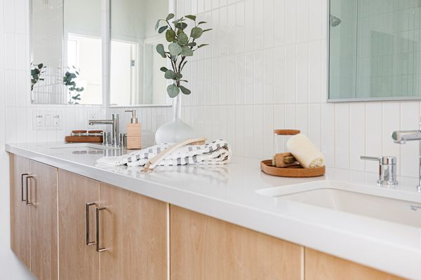 Bathroom countertop with white square edged treatment above light wood cabinets
