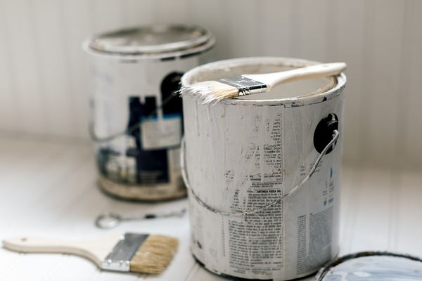 can of paint primer and brushes
