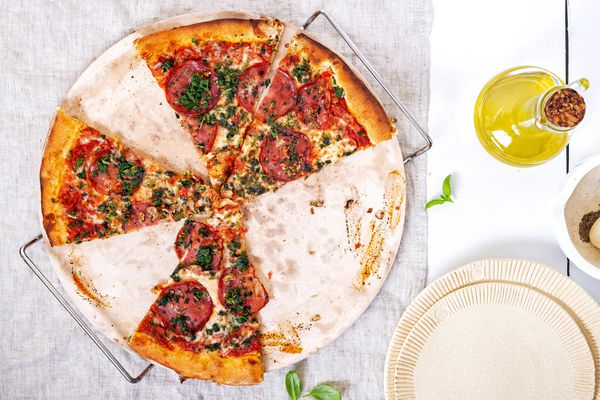 Pizza with tomatoes and basil on pizza stone next to bottle of olive oil