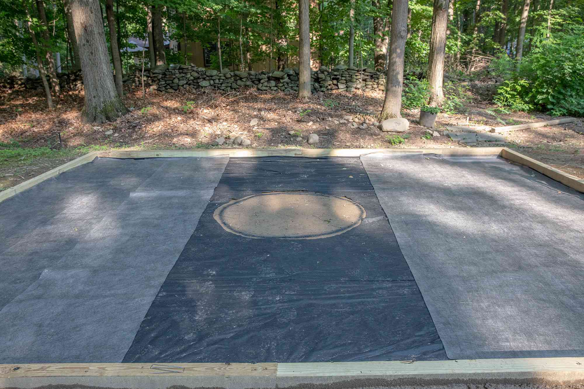 Fire pit location designated with landscape fabric and timbers
