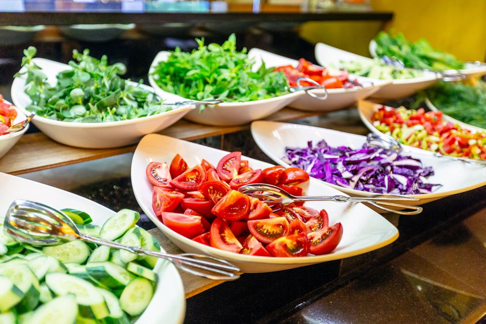 A salad bar with lettuce, tomatoes, cabbage, and cucumbers