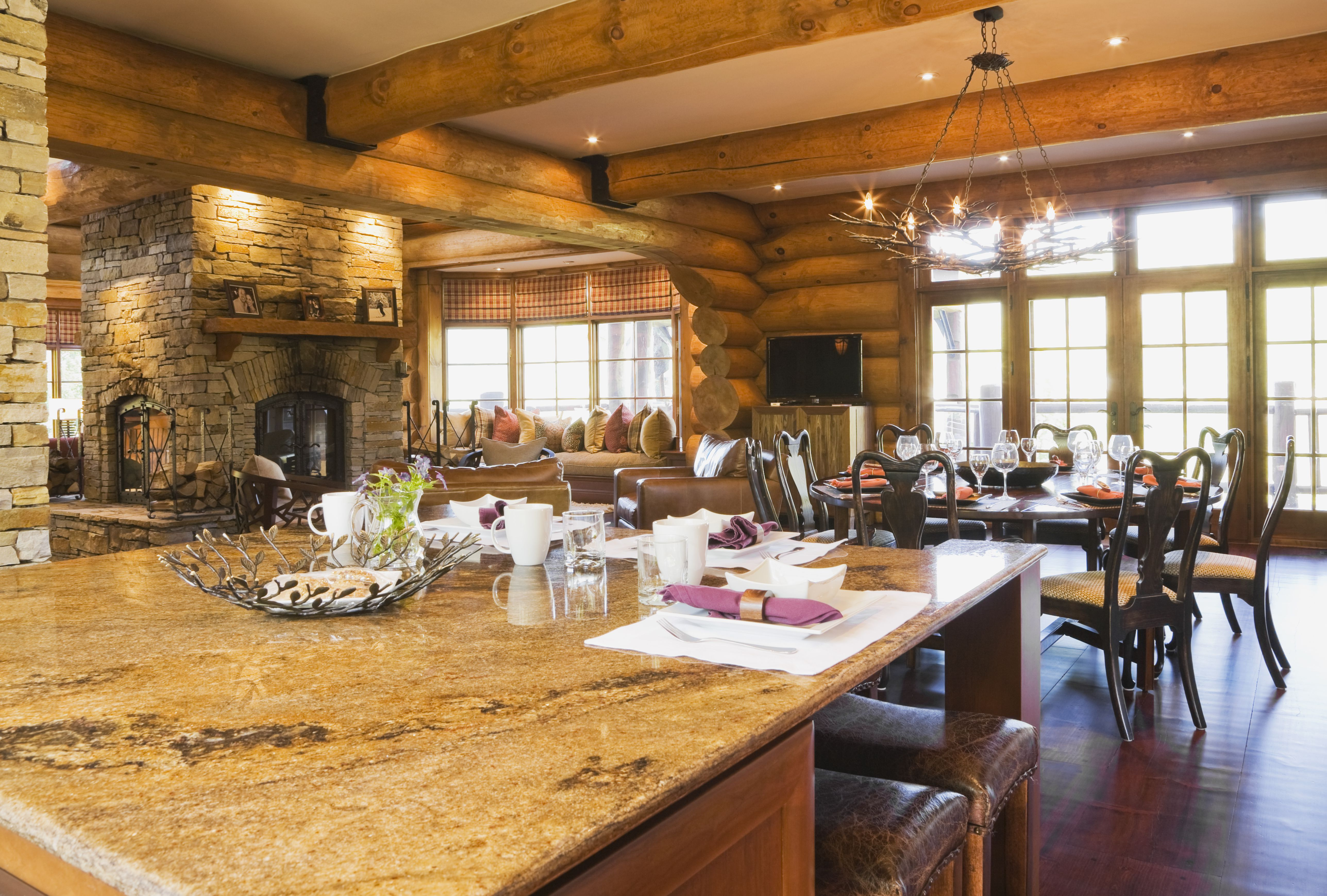 Island with granite countertop in kitchen and round wooden dining room table with 8 chairs inside a luxurious cottage style log home, Quebec, Canada.