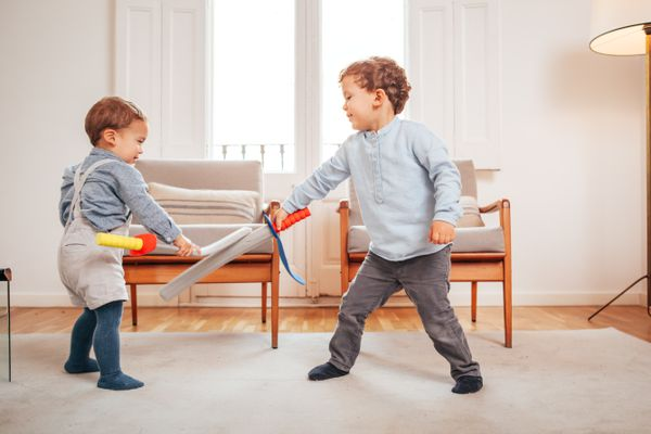 two young kids play fighting with foam swords